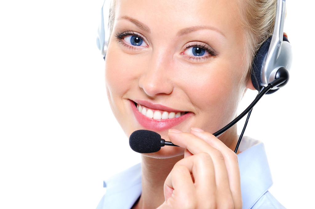 Happy smile of pretty young female operator with headphones