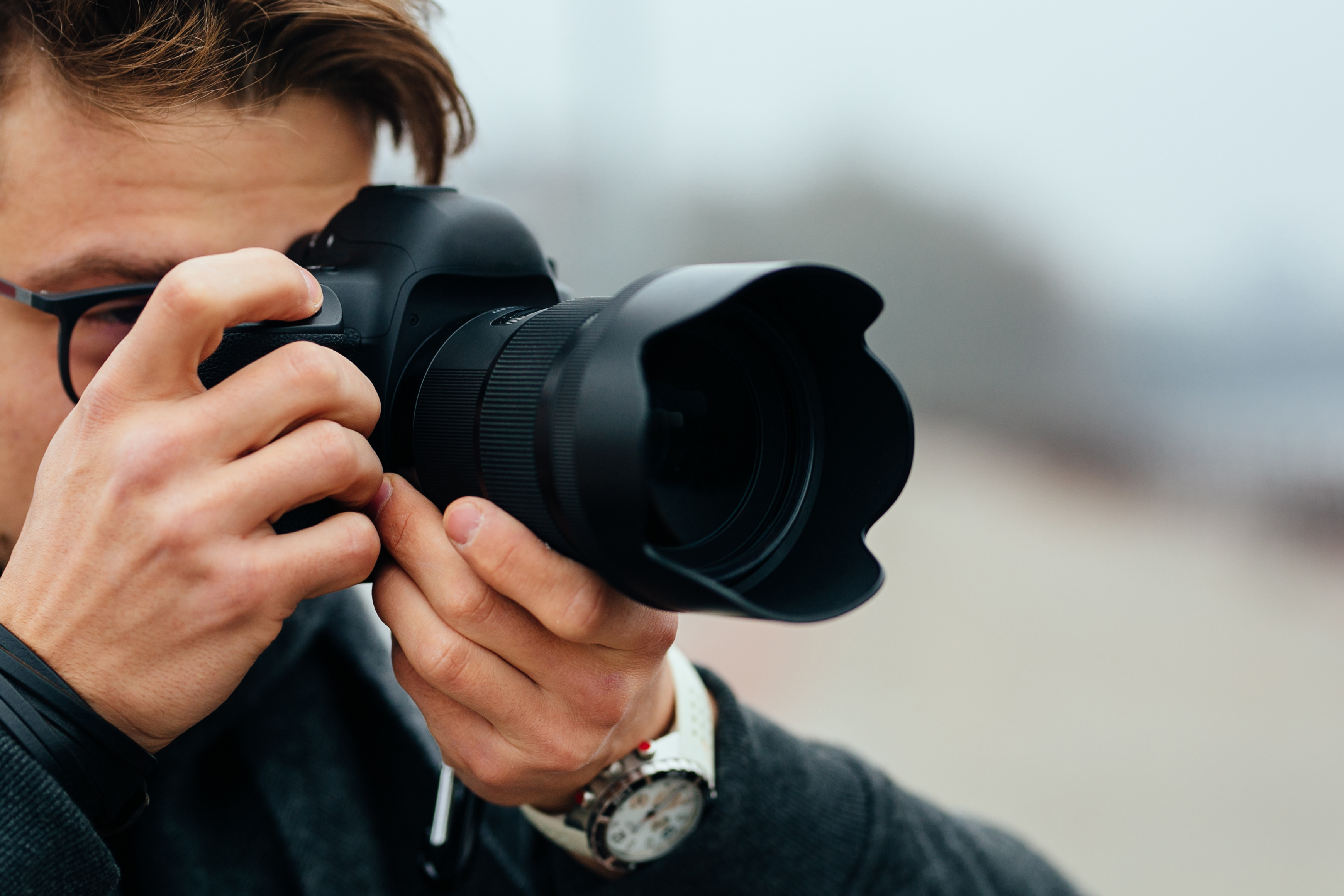 Detail view of young man in eyeglasses taking photos on the street. Dressed in warm jacket, fashinable white watches.
